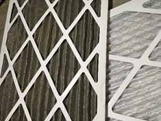 A clean air filter next to a dark and dirty air filter that could keep your AC from blowing cold air